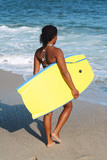 Young woman carrying her body board. poster