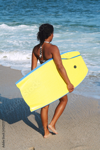 Young woman carrying her body board.
