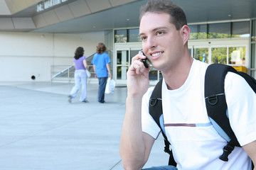 A handsome male college student smiling on his cell phone..