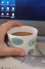Mans hand holding mug of coffee on office desk with computer