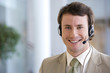 Young smiling businessman on headset