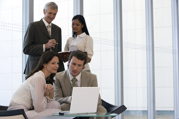 Business team of four with two on laptop