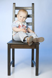 A 14 month old boy sitting on a chair poster