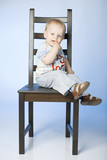 A 14 months old boy sitting on a chair poster