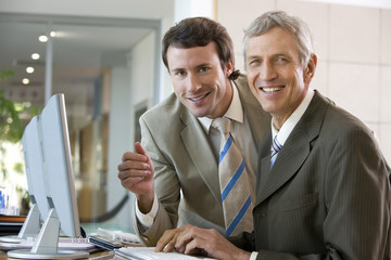 Businessman assisting another at computer