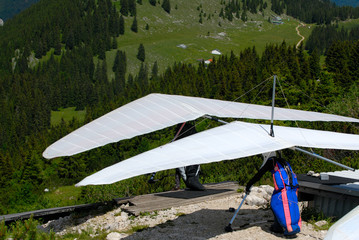 Two hang-gliders are waiting the wind on the start ramp