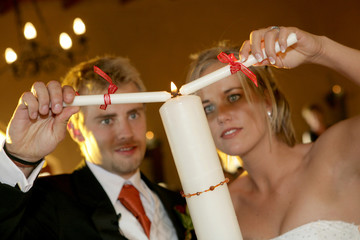 A bride and groom lighting a candle