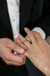 A groom putting a ring on his brides finger