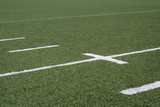White line markers on a green American football field.