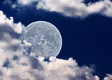 The moon in clouds on a background of the night sky.