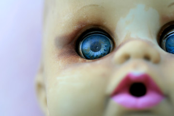 An extreme close up of a doll's face with shalow depth of field