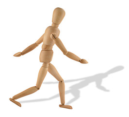 close-up of a running wooden figure with its shadow