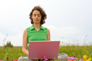 Girl working on the laptop in nature