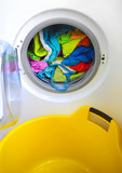 Close-up on a washing machine with clean colorful clothes poster