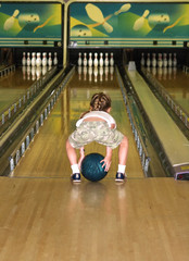 a little girl playing a game of bumper bowling