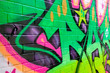 Graffiti with neon colors sprayed on a brick wall
