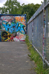 Graffiti on metal railings and a storage container.