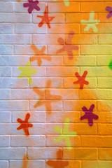 Graffiti with stars sprayed on a brick wall.