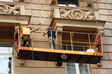 Two workers restoring old city building by tool poster