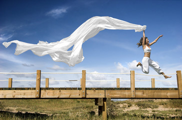 Young beautiful woman jumping with a scarf in a beautiful day