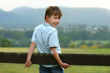 A young happy boy in the paddock on an overcast afternoon. f 3.5 poster