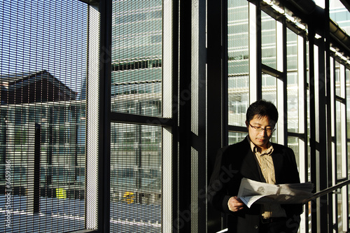 A businessman reading financial newspaper on a train station