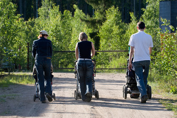 three people walking in the park  with baby carriages