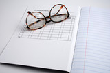 Pictures of glasses resting on a blank notepad, poster