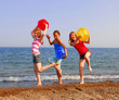 Three girls on a sandy beach being silly with colorful balls