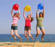Three girls on a sandy beach jumping with colorful balls
