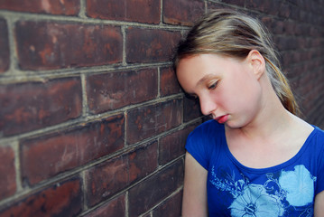Young girl near brick wall looking upset