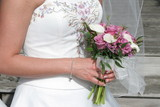 flower bouquet in hands with elegant white dress gown poster