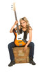 focus on guitara.Girl sitting on the box with bass guita