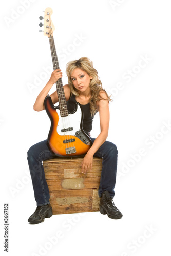focus on guitara.Girl sitting on the box with bass guita