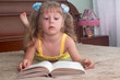 The girl reads the book on a bed