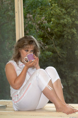 The woman sits on a window sill and drinks tea 2