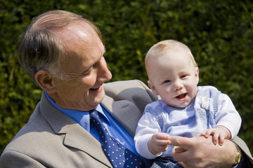 Grandfather holding smiling grandson in a sunlight garden
