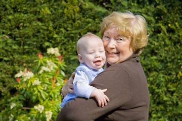 Grandmother hugging happy grandson in sunny garden
