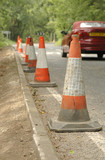 road safety cones and passing traffic poster