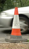 road safety cone and passing traffic poster