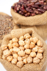 Burlap sack with chickpeas over a white background. Shallow DOF