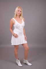 Beautiful blond woman in little white dress standing