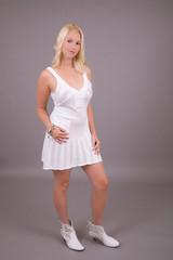 Beautiful blond woman in little white dress standing
