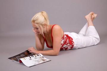 beautiful girl lying on the floor reading a magazine