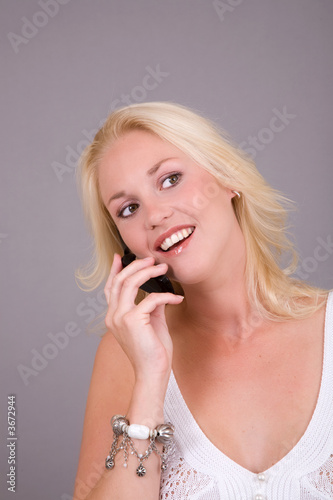 beautiful blond girl talking happily on the phone