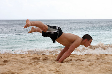 Young man doing handstand on the beach