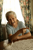 Retired elderly woman laughing and pointing at something poster