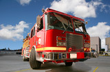 Fire engine on pavement with clouds in the background poster