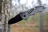 camouflage folding knife meant for hunting poster