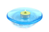 Burning candle on a blue glass dish - isolated on white. poster